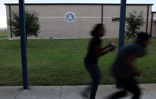 Randolph Secondary School students walk past a building with label indicating the school's past success in educating students on Thursday, Oct. 11, 2012. The school district is facing budget cuts to their Impact Aid funding come January. In light of the cuts, Randolph has cut several athletic programs along with some staff reductions. The independent school district has about 1,200 students from pre-Kindergarten to High School and is celebrating their 50th year in education. Photo: Kin Man Hui, San Antonio Express-News / © 2012 San Antonio Express-News