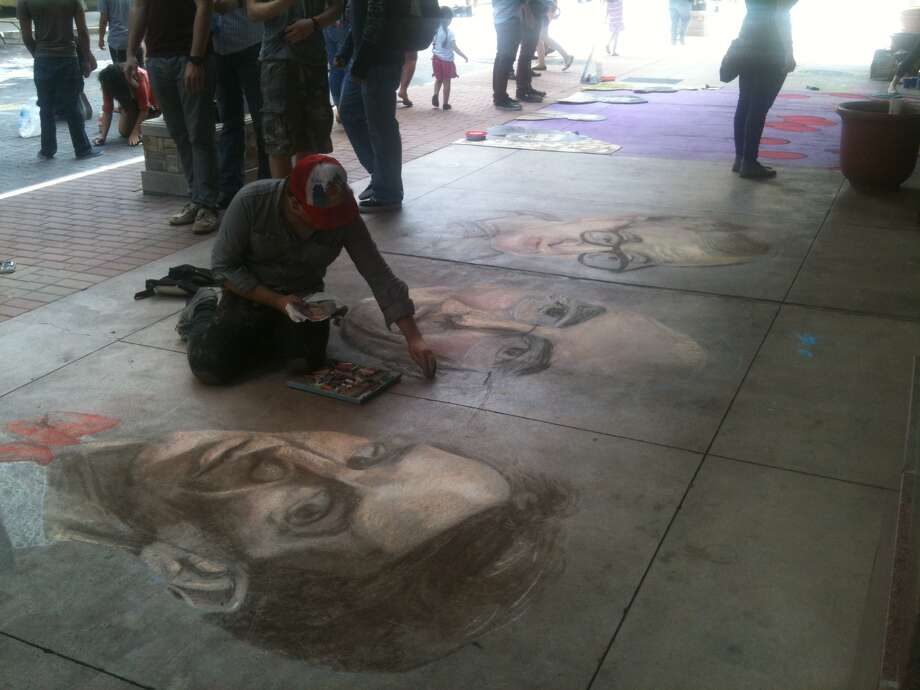 Artist Jeremiah Teutsch touches up three portraits at Chalk It Up 2012 on Saturday. Photo: Benjamin Olivo/mySA.com