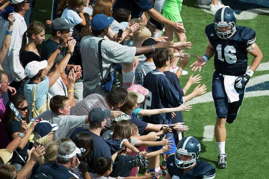 Rice quarterback Taylor McHargue (16) high fives fans as he takes the field before of a college foot