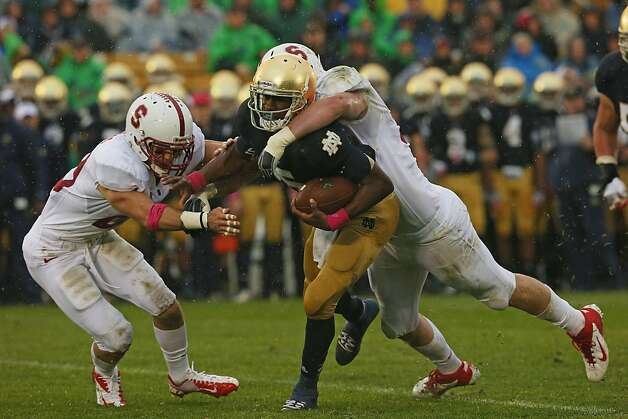 SOUTH BEND, IN - OCTOBER 13: Everett Golson #5 of the Notre Dame Fighting Irish is brought down by Henry Anderson #91 (R) and Ed Reynolds #29 of the Standford Cardinal at Notre Dame Stadium on October 13, 2012 in South Bend, Indiana. (Photo by Jonathan Daniel/Getty Images) Photo: Jonathan Daniel, Getty Images