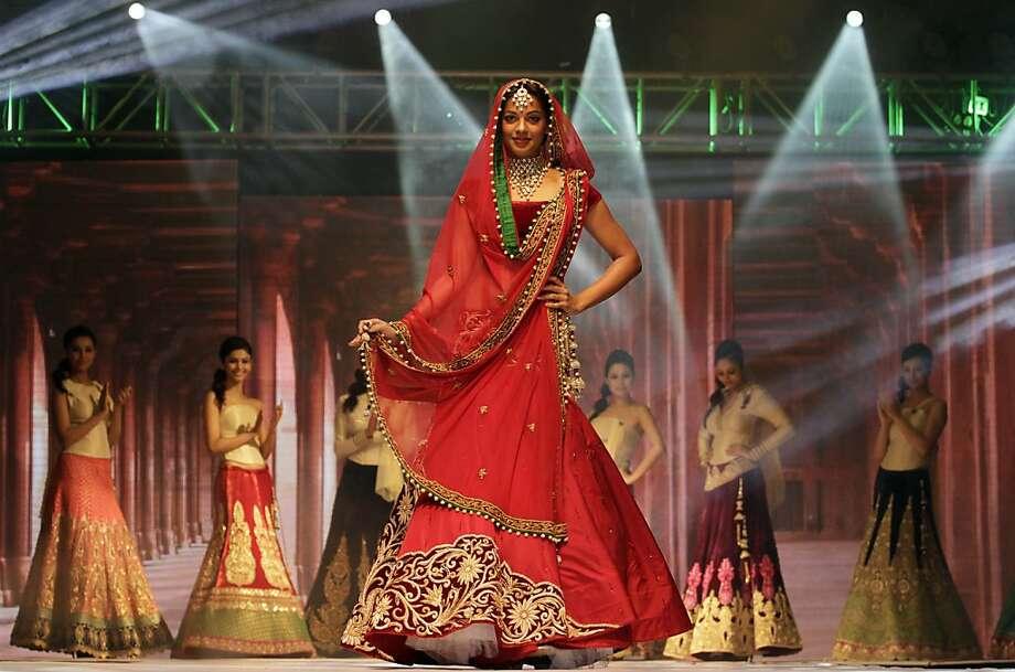 In this Friday, Oct. 12, 2012 photo, Bollywood actress Mugdha Godse displays a bridal wear during a bridal fashion show in Ahmadabad, India. (AP Photo/Ajit Solanki) Photo: Ajit Solanki, Associated Press