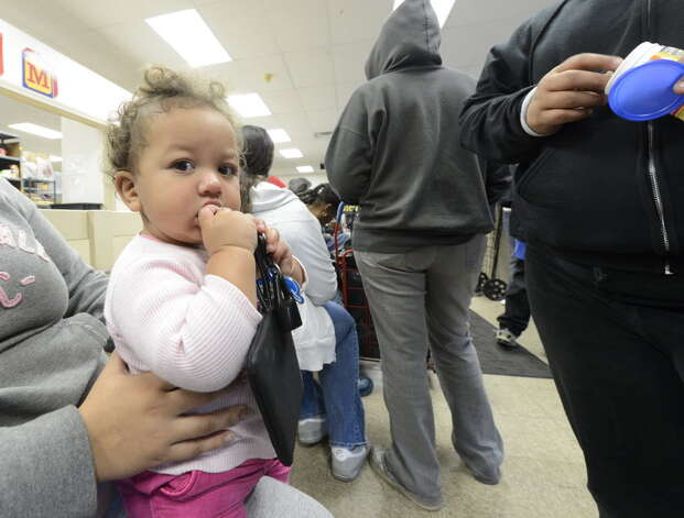 The presidential election has ignored the fate of children such as Evelis Sanchez, shown waiting for food with his mother last month at the Schenectady Inner City Mission in Schenectady. (Skip Dickstein/Times Union)