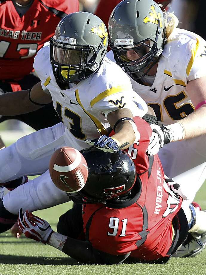 West Virginia's Andrew Buie (13) fumbles the ball after a hit by Texas Tech's Kerry Hyder, who had six tackles, one for a loss, in the Red Raiders' upset. Photo: Scott MacWatters, Associated Press
