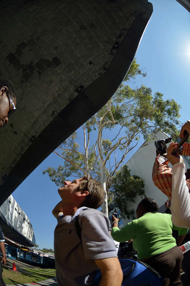 Spectators take a closer look at the wing of the Space Shuttle Endeavour as it passes by on Crenshaw Drive in Inglewood, Calif., Saturday, Oct. 13, 2012. Endeavour's 12-mile road trip kicked off shortly before midnight Thursday as it moved from its Los Angeles International Airport hangar en route to the California Science Center. (AP Photo/Los Angeles Newspaper Group, Jeff Gritchen, Pool) Photo: Jeff Gritchen, Associated Press