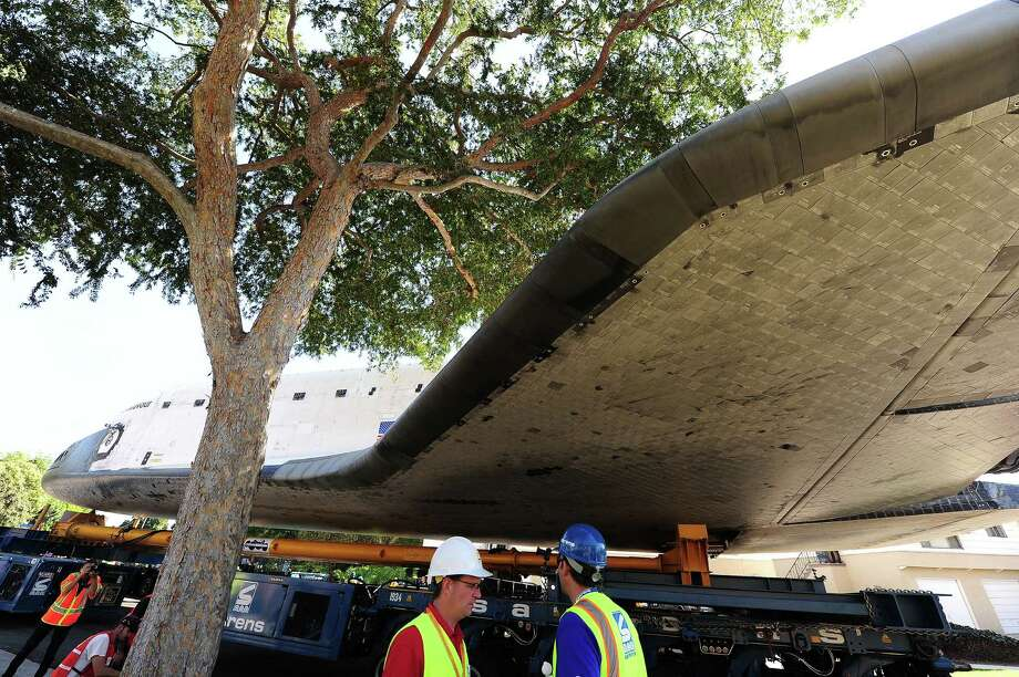 The Space Shuttle Endeavour's path is temporarily blocked by a tree as the shuttle is transported through the streets of Los Angeles and neighboring Inglewood on its final journey to its permanent museum home on October 13, 2012 in Inglewood, California. The 170,000-pound shuttle will travel at no more than 2 mph along a 12-mile route from Los Angeles International Airport to its final home at the California Science Center.     AFP PHOTO / Robyn Beck Photo: ROBYN BECK, AFP/Getty Images / AFP