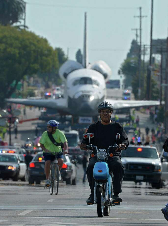 A man on a bike and a man on a moped ride in front of the space shuttle Endeavour as it is slowly moved down Crenshaw Blvd., Saturday, Oct.13, 2012, in Los Angeles. The shuttle is on its last mission — a 12-mile creep through city streets. It will move past an eclectic mix of strip malls, mom-and-pop shops, tidy lawns and faded apartment buildings. Its final destination: California Science Center in South Los Angeles where it will be put on display. (AP Photo/Mark J. Terrill) Photo: Mark J. Terrill, Associated Press / AP