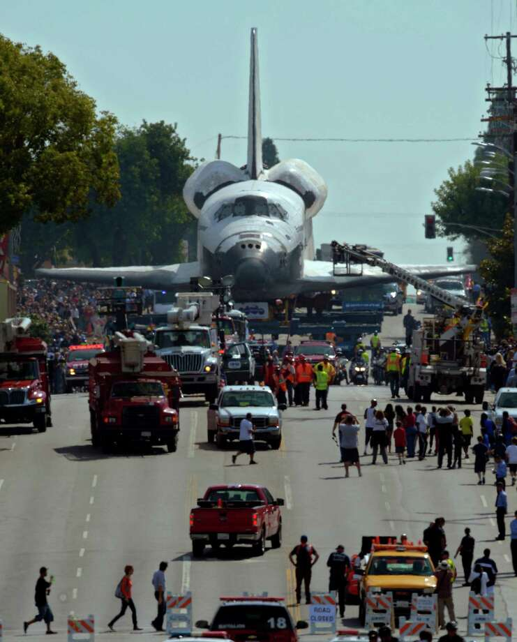 The space shuttle Endeavour is slowly moved down Crenshaw Blvd., Saturday, Oct.13, 2012, in Los Angeles. The shuttle is on its last mission — a 12-mile creep through city streets. It will move past an eclectic mix of strip malls, mom-and-pop shops, tidy lawns and faded apartment buildings. Its final destination: California Science Center in South Los Angeles where it will be put on display. (AP Photo/Mark J. Terrill) Photo: Mark J. Terrill, Associated Press / AP
