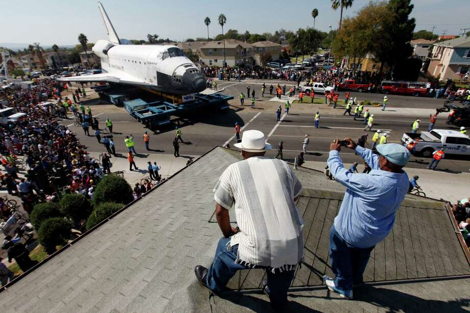 The space shuttle Endeavour makes its way down Crenshaw Boulevard in Inglewood, Calif., Saturday, Oct. 13, 2012. Endeavour's 12-mile road trip kicked off shortly before midnight Thursday as it moved from its Los Angeles International Airport hangar en route to the California Science Center. (AP Photo/Patrick T. Fallon) Photo: Patrick T. Fallon, Associated Press / FR160581 AP