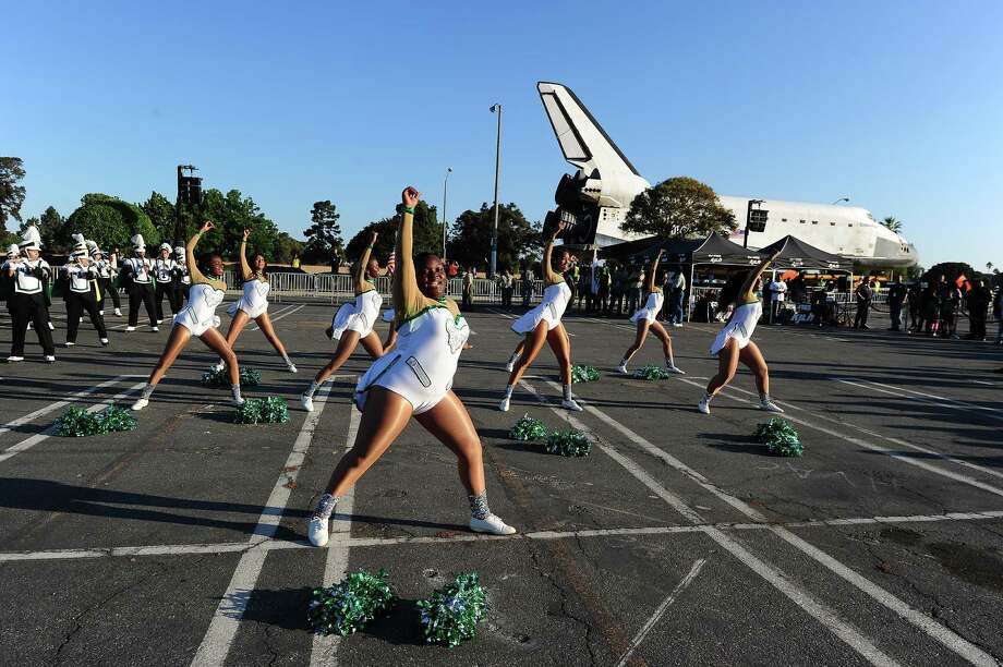 Inglewood High School cheerleaders perform in front of the Space Shuttle Endeavour as it is transported through the streets of Inglewood and Los Angeles on its final journey to its permanent museum home on October 13, 2012 in Los Angeles. . AFP PHOTO / Robyn Beck Photo: ROBYN BECK, AFP/Getty Images / AFP