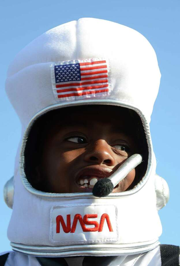 Darius Williams wears an astronaut costume in front of the Space Shuttle Endeavour as it is transported through the streets of Los Angeles on its final journey to its permanent museum home, October 13, 2012 in Los Angeles, California.  AFP PHOTO / Robyn Beck Photo: ROBYN BECK, AFP/Getty Images / AFP