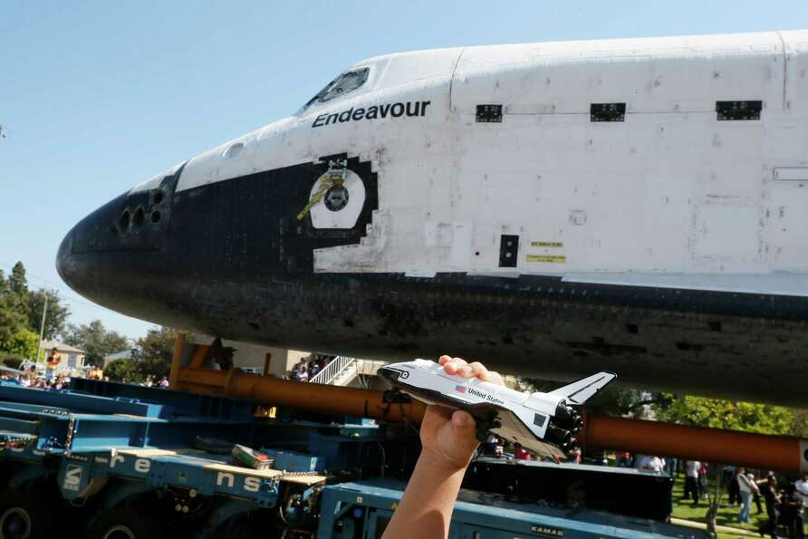 A boy holds a model of the space shuttle Endeavour near the shuttle as it is moved to the California