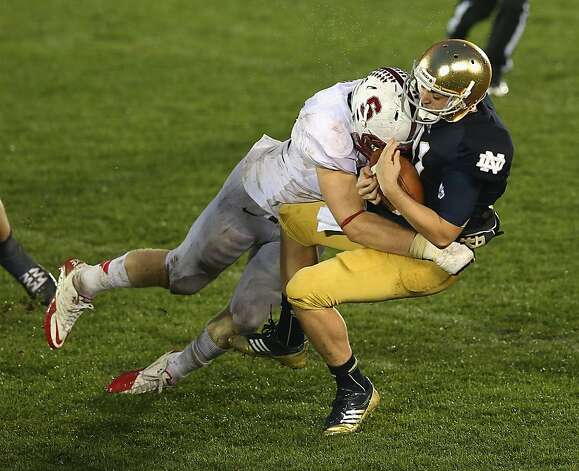 Stanford's Trent Murphy administers an overtime sack to Notre Dame's Tommy Rees, a fourth-quarter entrant. Photo: Jonathan Daniel, Getty Images
