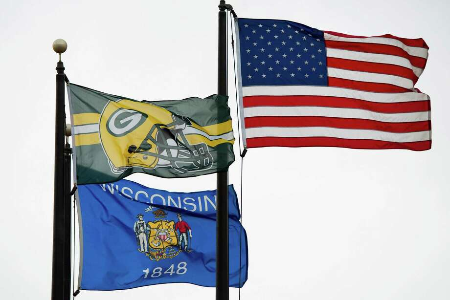 A Green Bay Packers flag gets prominent display alongside The Stars and Stripes and the Wisconsin state flag at a business park in Pewaukee,Wis., hometown of Houston Texans defensive end J.J. Watt. Photo: Smiley N. Pool, Houston Chronicle / © 2012  Houston Chronicle