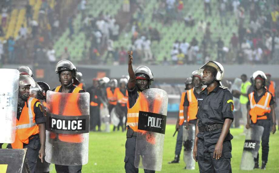 Senegalese police watch rampagng fans on October 13, 2012 at Léopold Sédar Senghor stadium in Dakar during Senegal's African Cup of Nations qualifier against Ivory Coast. The match was abandoned after home fans went on a violent rampage as their team slipped towards a humiliating defeat. Fires were set in the stands while stones, chairs and bottles were thrown at the players, an AFP journalist witnessed, after Ivory Coast went 2-0 ahead, 15 minutes from the end of the second leg of the tie.     AFP PHOTO/SEYLLOU Photo: SEYLLOU, AFP/Getty Images / AFP