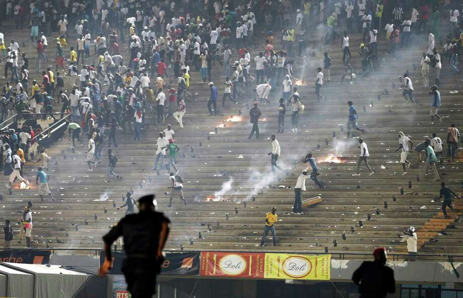Riot police run to respond as Senegal fans throw rocks and set fires in the stands at Leopold Sedar Senghor Stadium, during an African Cup of Nations qualifier against Ivory Coast, in Dakar, Senegal, Saturday, Oct. 13, 2012. Fans rioted after Ivory Coast's Didier Drogba scored a second goal on a penalty, effectively eliminating Senegal from the 2013 Cup of Nations tournament. The game was suspended with roughly 15 minutes remaining, and riot police had to escort Ivory Coast players from the field. (AP Photo/Rebecca Blackwell) Photo: Rebecca Blackwell, Associated Press / AP
