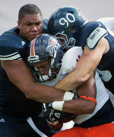 Rice 34 - UTSA 14: Rice defensive tackle Christian Covington, left, and defensive end Cody Bauer (90) bring down UTSA running back David Glasco II (11) during the first quarter of a college football game at Rice Stadium, Saturday, Oct. 13, 2012, in Houston. Photo: Smiley N. Pool, Houston Chronicle / © 2012  Houston Chronicle