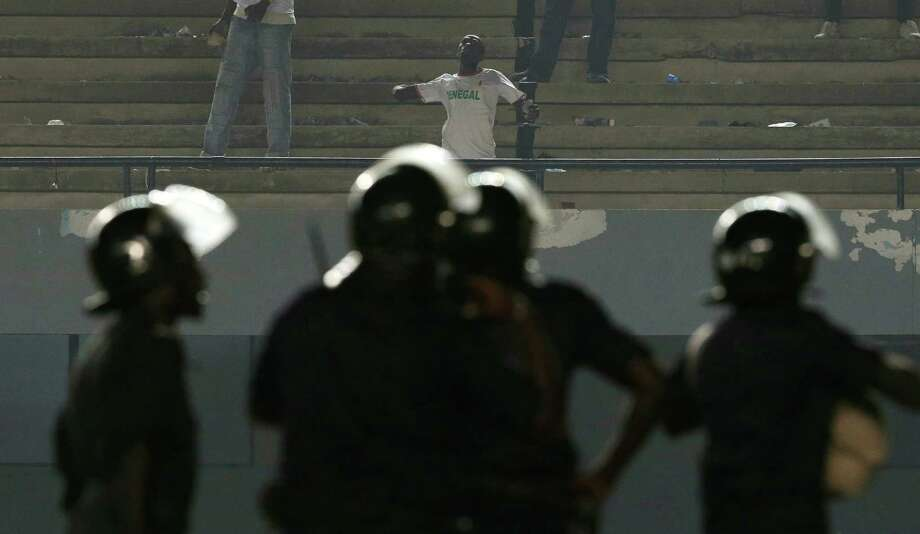 A fan in a Senegal tee-shirt hurls rocks toward police, after rioting Senegal fans caused Ivory Coast's African Cup of Nations qualifier against Senegal to be suspended, at Leopold Sedar Senghor Stadium in Dakar, Senegal, Saturday, Oct. 13, 2012.  (AP Photo/Rebecca Blackwell) Photo: Rebecca Blackwell, Associated Press / AP