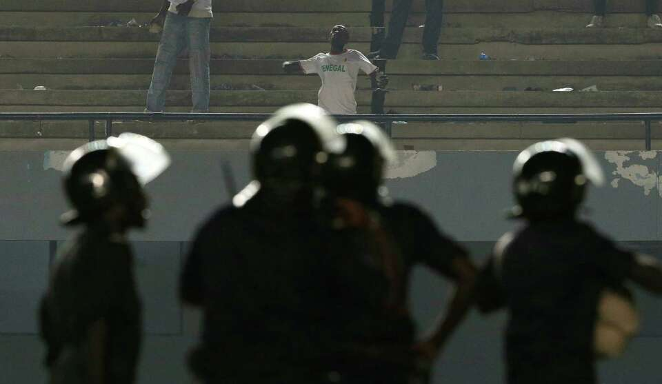 A fan in a Senegal tee-shirt hurls rocks toward police, after rioting Senegal fans caused Ivory Coas