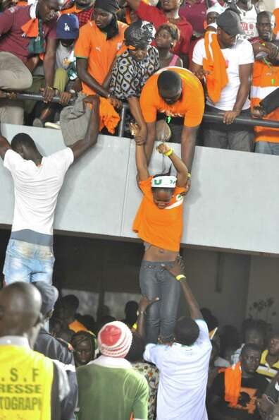 Ivory Coast fans are evacuated onto the field as Senegalese supporters rampage on October 13, 2012 a