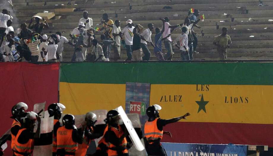 Riot police throw rocks back into the stands as fans rioted, throwing objects onto the field and lighting fires, during an African Cup of Nations qualifier against Ivory Coast, at Leopold Sedar Senghor Stadium in Dakar, Senegal, Saturday, Oct. 13, 2012.  (AP Photo/Rebecca Blackwell) Photo: Rebecca Blackwell, Associated Press / AP