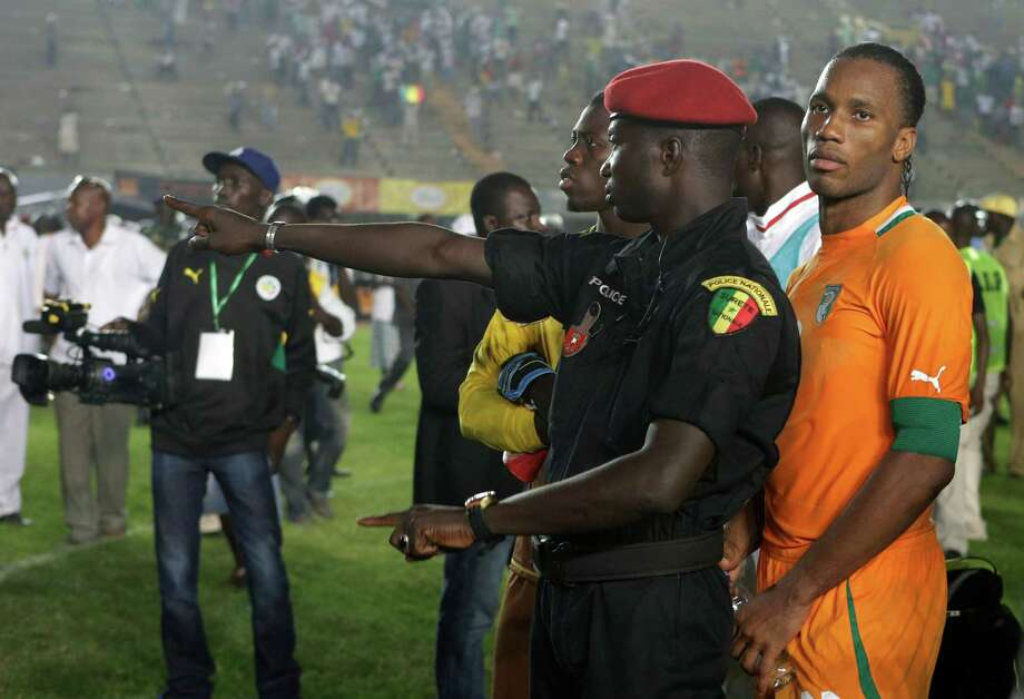 A Senegalese policeman stands guard in front of Ivory Coast captain Didier Drogba, after rioting Senegal fans caused Ivory Coast's African Cup of Nations qualifier against Senegal to be suspended, at Leopold Sedar Senghor Stadium in Dakar, Senegal, Saturday, Oct. 13, 2012.  (AP Photo/Rebecca Blackwell) Photo: Rebecca Blackwell, Associated Press / AP