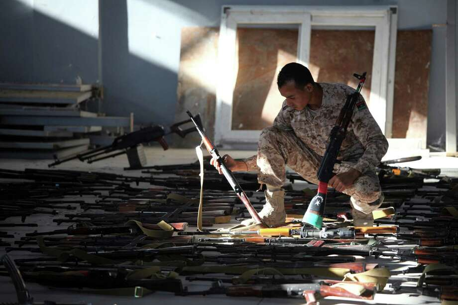 A Libyan soldier checks weapons handed in by rebel fighters and civilians, at a military compound in Tripoli, Libya, Sept. 3, 2012. The weak Libyan government faces the task of trying to bring militias to heel while depending on them as the only armed forces, a conundrum that has trapped the country in a state of lawlessness. (Mohammad Hannon/Associated Press for The New York Times) Photo: MOHAMMAD HANNON/ASSOCIATED PRESS / ASSOCIATED PRESS