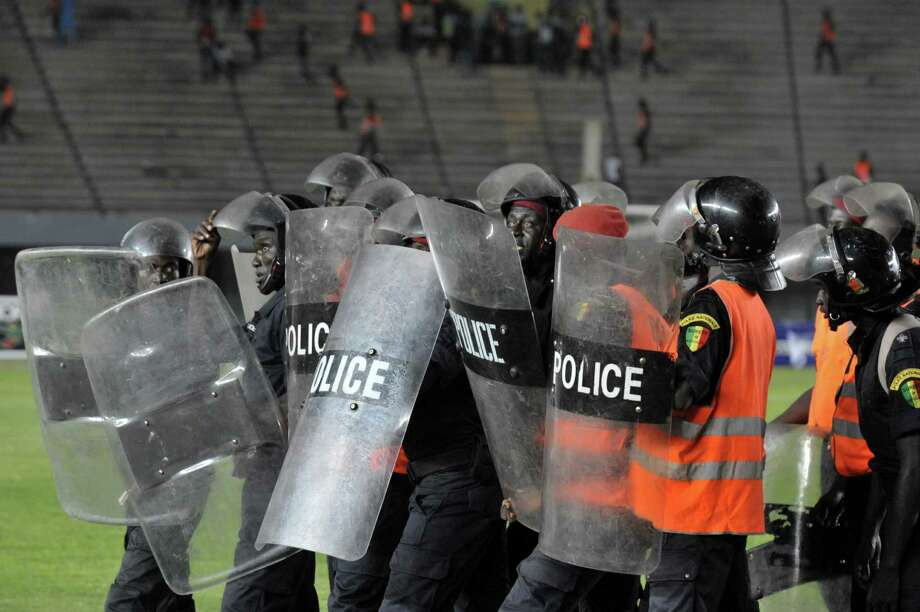 Senegalese police move in as fans rampage on October 13, 2012 at Léopold Sédar Senghor stadium in Dakar during Ivory Coast's African Cup of Nations qualifier against Senegal.     AFP PHOTO/SEYLLOU Photo: SEYLLOU, AFP/Getty Images / AFP