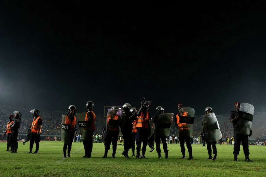 Riot police stand on the playing field ready to respond after Senegal fans rioted in the stands, throwing rocks and lighting fires, during an African Cup of Nations qualifier against Ivory Coast, at Leopold Sedar Senghor Stadium in Dakar, Senegal, Saturday, Oct. 13, 2012.  (AP Photo/Rebecca Blackwell) Photo: Rebecca Blackwell, Associated Press / AP
