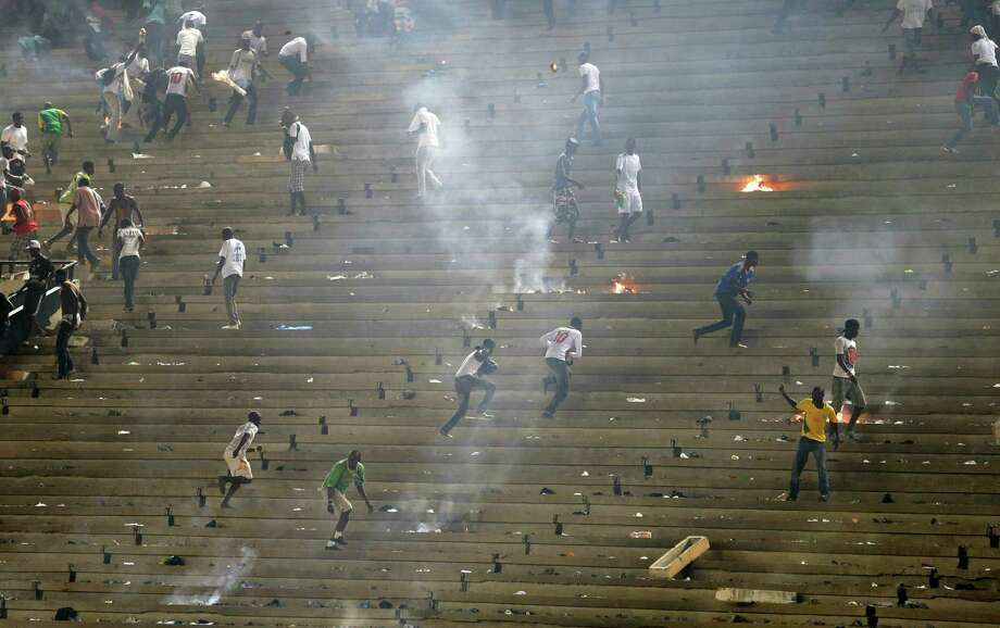 Rioting fans run as police respond from the field at Leopold Sedar Senghor Stadium, during an African Cup of Nations qualifier against Ivory Coast, in Dakar, Senegal, Saturday, Oct. 13, 2012. (AP Photo/Rebecca Blackwell) Photo: Rebecca Blackwell, Associated Press / AP