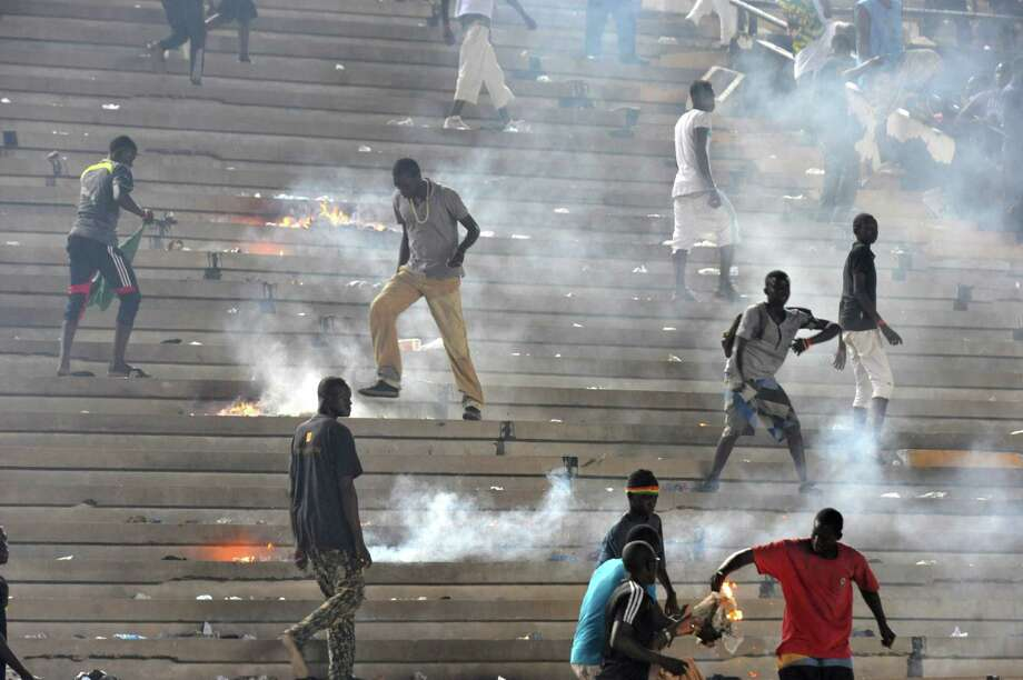 Fans set fire to stands on October 13, 2012 at Léopold Sédar Senghor stadium in Dakar during Ivory Coast's African Cup of Nations qualifier against Senegal.      AFP PHOTO/SEYLLOU Photo: SEYLLOU, AFP/Getty Images / AFP