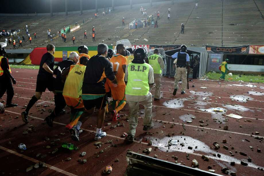Riot police surround a group of Ivory Coast players, including Siaka Tiene, number 17, as they rush them off the field after clearing rioting Senegal fans from the stands above the players' tunnel, at Leopold Sedar Senghor Stadium in Dakar, Senegal, Saturday, Oct. 13, 2012.  (AP Photo/Rebecca Blackwell) Photo: Rebecca Blackwell, Associated Press / AP