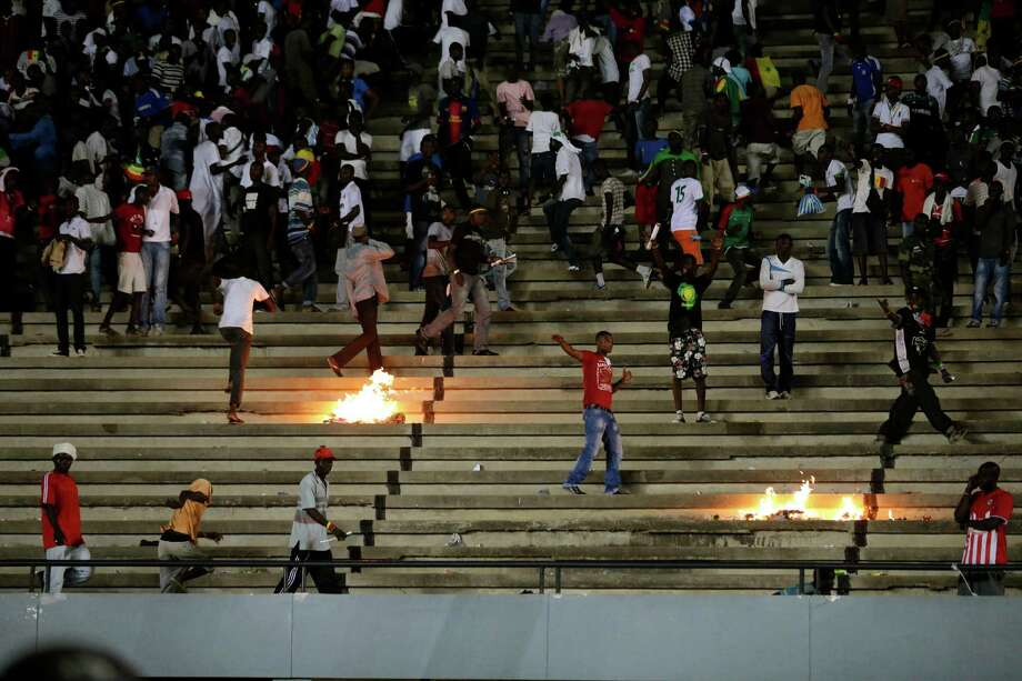 Senegal fans throw rocks and set fires in the stands at Leopold Sedar Senghor Stadium during an African Cup of Nations qualifier against Ivory Coast, in Dakar, Senegal, Saturday, Oct. 13, 2012. . (AP Photo/Rebecca Blackwell) Photo: Rebecca Blackwell, Associated Press / AP