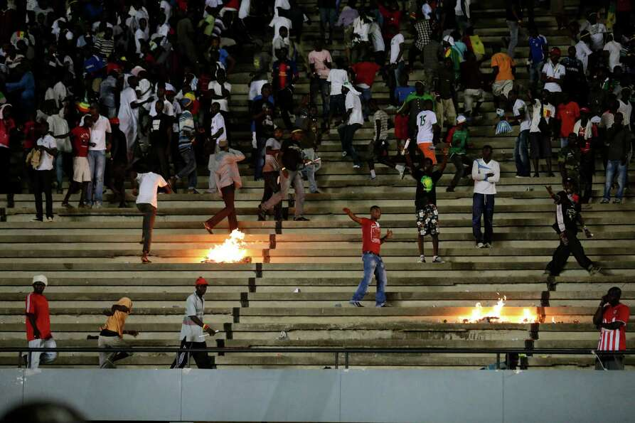 Senegal fans throw rocks and set fires in the stands at Leopold Sedar Senghor Stadium during an Afri