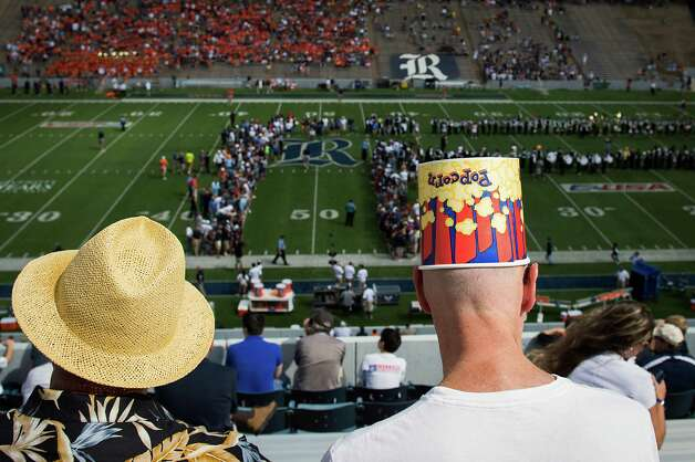 Andrew Wilking uses a popcorn container to shield his head from the afternoon sun before a college football game between Rice and UTSA at Rice Stadium, Saturday, Oct. 13, 2012, in Houston. Photo: Smiley N. Pool, Houston Chronicle / © 2012  Houston Chronicle