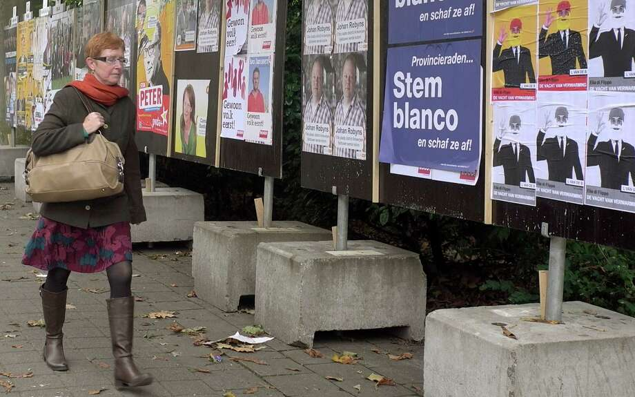 In this photo taken on Monday, Oct. 8, 2012, a woman walks by election campaign posters in Antwerp, Belgium. Historic world port and hip fashionista capital, Antwerp has always lived on the crest of the wave. Now, a separatist Fleming is seeking to make the city his own on Sunday and use it as a base for breaking away from Belgium. Local elections will take place on Sunday, Oct. 14, 2012. Poster reads on second right, 'Vote Blank and annul the election'. (AP Photo/Virginia Mayo) Photo: Virginia Mayo