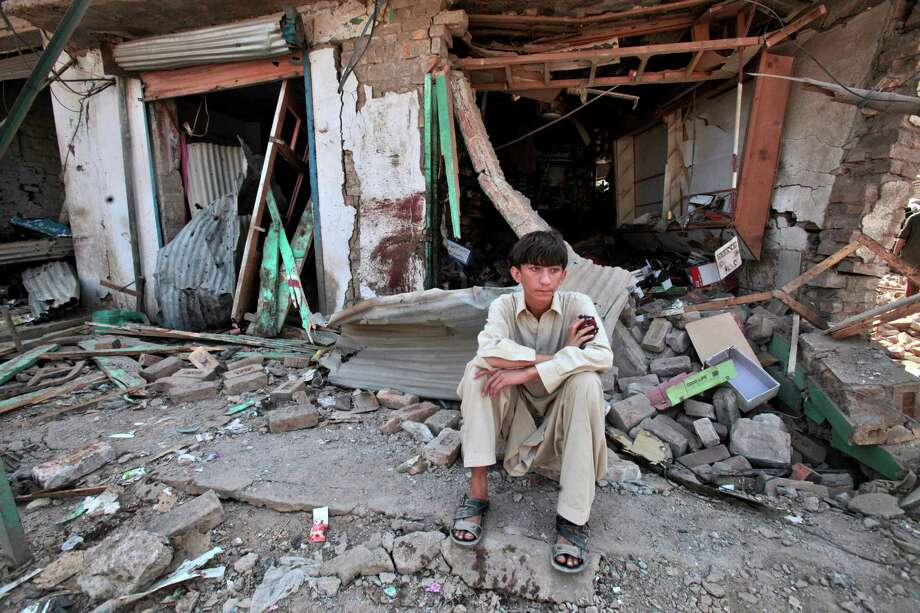 A Pakistani youth sits amid the rubble of offices destroyed in a car bomb explosion in the Pakistani town of Darra Adam Khel in the troubled Khyber Pakhtunkhwa province bordering Afghanistan, Saturday, Oct. 13, 2012. A powerful car bomb went off outside the offices of pro-government tribal elders in northwestern Pakistan on Saturday, killing several people, police said. (AP Photo/Mohammad Sajjad) Photo: Mohammad Sajjad
