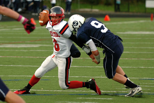 Wilton's #9 Griffin Bender sacks McMahon QB Matt Downey, during boys football action in Wilton, Conn. on Friday October 13, 2012. Photo: Christian Abraham / Connecticut Post