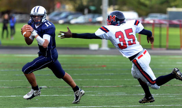 McMahon's #35 Allan Leonard tries but fails to grab a hold of Wilton QB #11 Brett Phillips, during boys football action in Wilton, Conn. on Friday October 13, 2012. Photo: Christian Abraham / Connecticut Post