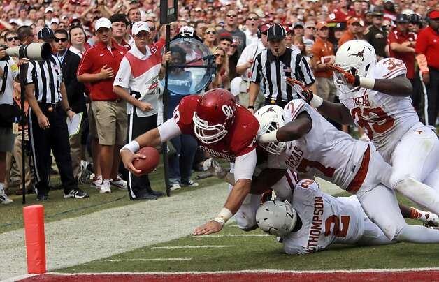 Oklahoma quarterback Blake Bell stretches for the goal line in scoring a touchdown against Texas linebacker Steve Edmond (33), defensive back Mykkele Thompson (2) and linebacker Demarco Cobbs (7) in Dallas. Photo: Michael Mulvey, Associated Press