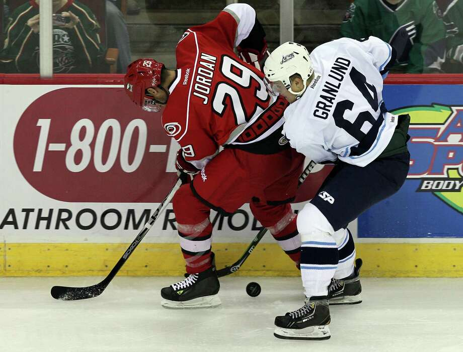 Michal Jordan #29 of the Charlotte Checkers is pressured along the sideboards by Mikael Granlund #64 of the Houston Aeros during the first period of an AHL hockey game between the the Charlotte Checkers and the Houston Aeros, Saturday, October 13 2012 at the Toyota Center in Houston, Texas. (Bob Levey/For The Chronicle) Photo: Bob Levey, Houston Chronicle / ©2012 Bob Levey