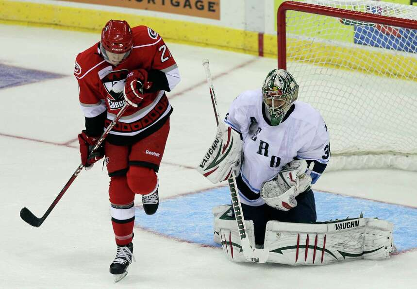 Goalie Matt Hackett #31 of the Houston Aeros  stops a shot as Riley Nash #20 of the Charlotte Checke