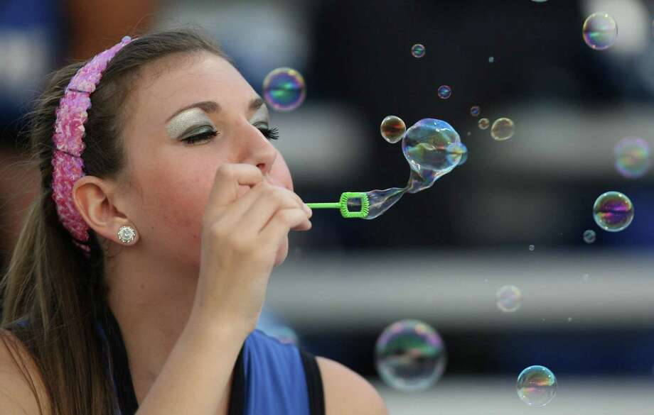 Westside Pride drill team member Rachel Long blows bubbles in the stands during the first half of a high school football game against Lamar, Saturday, October 13, 2012 at Delmar Stadium in Houston, TX. Photo: Eric Christian Smith, For The Chronicle