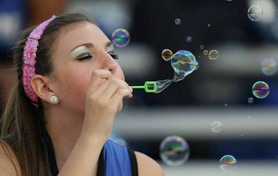 Westside Pride drill team member Rachel Long blows bubbles in the stands during the first half of a