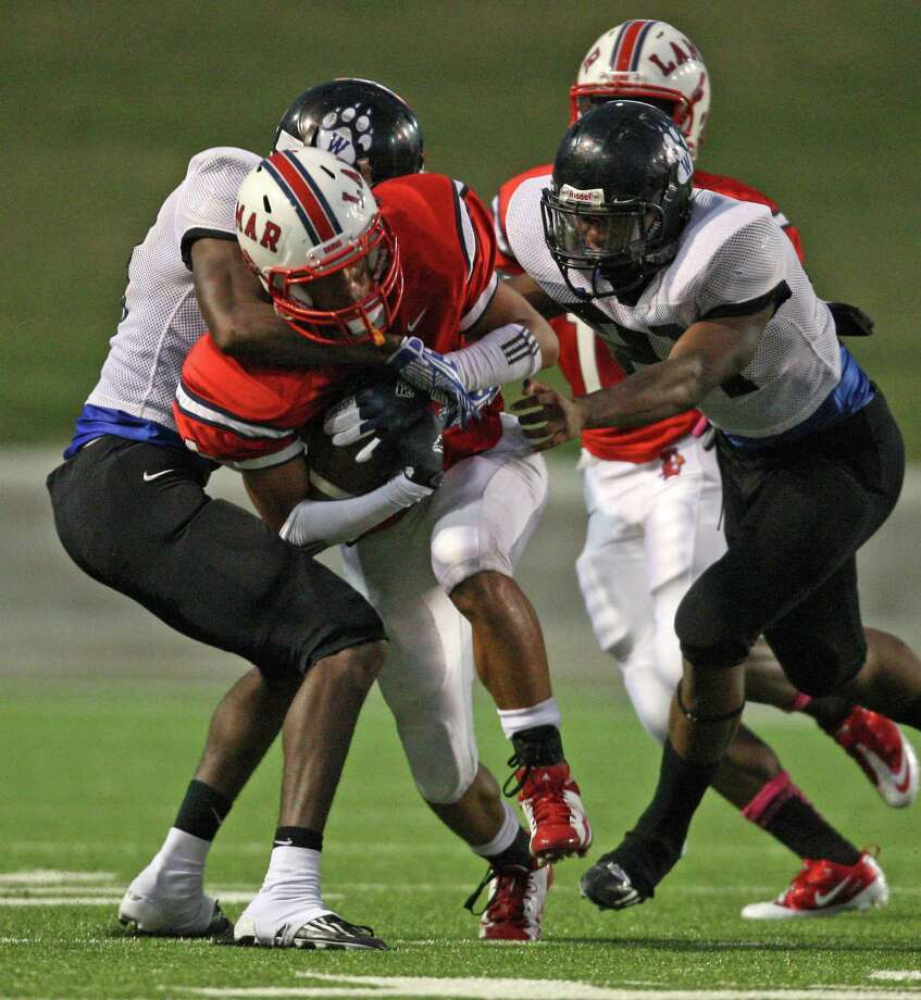Lamar's John Bonney is tackled by Westside's Myles Lattin (left) and Loren Easly during the first half of a high school football game, Saturday, October 13, 2012 at Delmar Stadium in Houston, TX. Photo: Eric Christian Smith, For The Chronicle