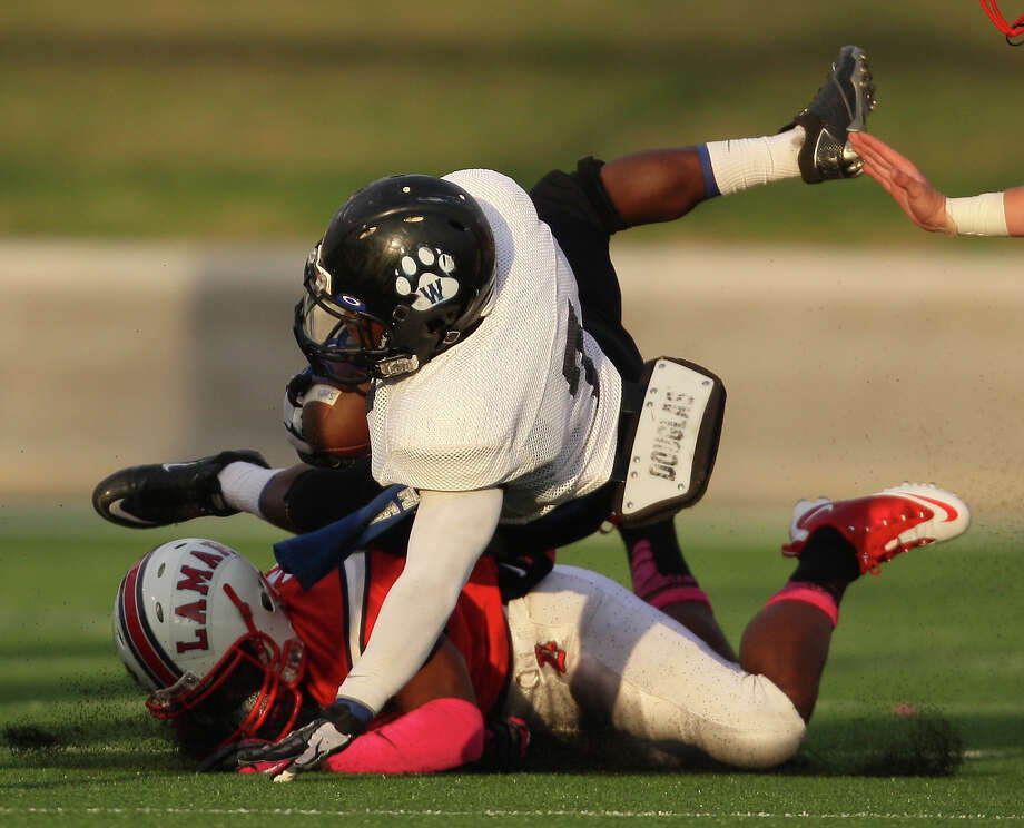 Westside running back Xavier Holman (7) is tackled by Lamar defensive back Cedric Lancaster during the first half of a high school football game, Saturday, October 13, 2012 at Delmar Stadium in Houston, TX. Photo: Eric Christian Smith, For The Chronicle