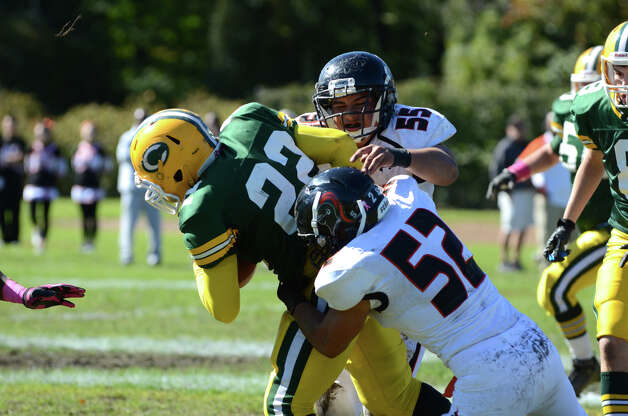 Stamford's Miguel Nieto (52) and Rodrigo Denapoli (55) take down Trinity's Shaquan Howsie (22) during the football game at Trinity Catholic High School in Stamford on Saturday, Oct. 13, 2012. Photo: Amy Mortensen / Connecticut Post Freelance