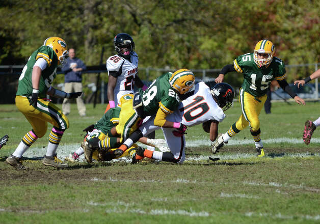 Trinity's Rany Polonia (28) tackles Stamford's John Pasard (10) during the football game at Trinity Catholic High School in Stamford on Saturday, Oct. 13, 2012. Photo: Amy Mortensen / Connecticut Post Freelance