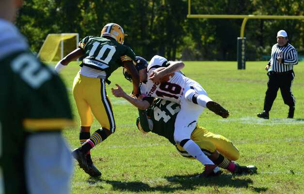 Trinity's David Deleo (42) takes down Stamford's Tyler Kane (18) during the football game at Trinity Catholic High School in Stamford on Saturday, Oct. 13, 2012. Photo: Amy Mortensen / Connecticut Post Freelance