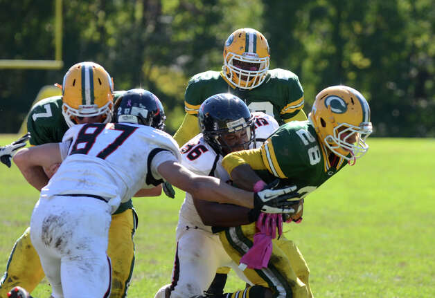 Trinity's Randy Polonia (28) is tackled by Stamford's Ryan Lapotts (36) during the football game at Trinity Catholic High School in Stamford on Saturday, Oct. 13, 2012. Photo: Amy Mortensen / Connecticut Post Freelance