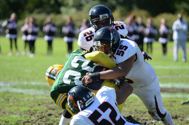 Stamford's Rodrigo Denapoli (55) Miguel Nieto (52) and Devaun Joyner (26) take down Trinity's Shaquan Howsie (22) during the football game at Trinity Catholic High School in Stamford on Saturday, Oct. 13, 2012. Photo: Amy Mortensen / Connecticut Post Freelance
